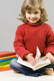 Beatiful girl reading book. Little girl and colored books royalty free stock photo