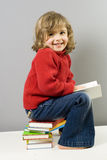 Beatiful girl reading book. Little girl and colored books stock photos