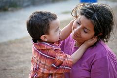 Beatiful Hispanic mother and child. Beautiful Hispanic mother and child holding his mother's face Royalty Free Stock Photo