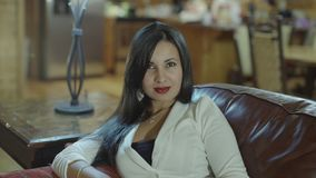 Beatiful hispanic young woman sitting on a couch. Slow motion.  stock footage