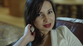 Beatiful hispanic young woman sitting on a couch. Slow motion.  stock video footage