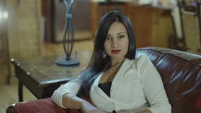 Beatiful hispanic young woman sitting on a couch. Slow motion.  stock video