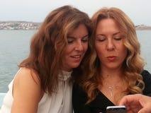 Beatiful ladies. Two ladies looking to phone stock images
