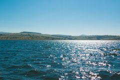 Beatiful Lake with the blue sky at High noon. Blue lake with some mountains in background royalty free stock images