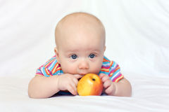 Beatiful little boy with apple. Photo of lying little boy with red-yellow apple Stock Images