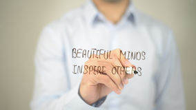 Beatiful Minds Inspire Others , man writing on transparent screen stock image