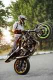 Beatiful sideview of biker riding motorcycle in extreme way. stock photos