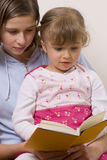 Beatiful sisters reading book. Little girl and color book Royalty Free Stock Photography