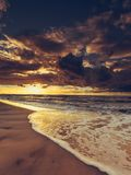 Beatiful sunset with clouds over sea and beach Stock Photos
