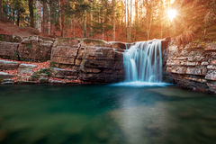 Beatiful sunset in the forest near waterfall Royalty Free Stock Photos