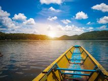 Beatiful sunset in lake with wooden boat stock photo