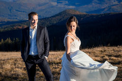 Beatiful wedding couple posing on the top of mountain. Sunny day Stock Photos