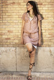 Beatiful woman leaning against a brick wall Stock Photos