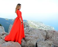 Woman in long red dress on the edge of a cliff in the mountains. Peak of Ai-Petri mountain. Beatiful woman in long red dress on the edge of a cliff in the Royalty Free Stock Photos