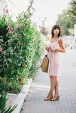 Beatiful woman in a pink dress posing near pink flowers Royalty Free Stock Photography