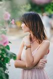 Beatiful woman in a pink dress posing near pink flowers Stock Photography
