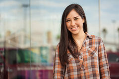 Beatiful young woman outside a clothing store. Portrait of a cute young Hispanic brunette dressed casual and standing outside a clothing store in a shopping mall Royalty Free Stock Images
