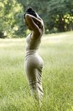 Beatiful young woman posing in tall golden grass. African American woman standing alone in an open grassy field royalty free stock image
