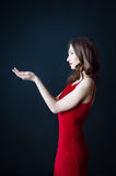 Beatiful young woman in red dress holding something in her hands Stock Photography