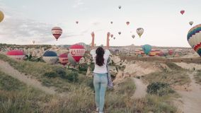 Young woman sunrise staying on the mountain with hot air ballons around. Steady cam shot
