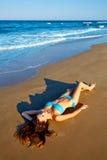 Beatifull donkerbruin meisje die op strandzand liggen Stock Afbeelding