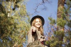 Beatifull dziewczyny obsiadanie w lesie i robić ok Zdjęcie Stock