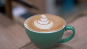 Beatifully bereidde hete latte met bladontwerp in voor een turkooise kop met perfect crema en schuim Sluit omhoog stock footage