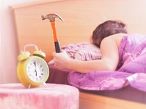 Beating the alarm clock with hammer. concept of sleep stock image