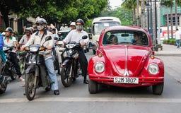 Beatle vermelho velho que está na estrada transversal Fotografia de Stock Royalty Free