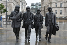 The Beatles. Bronze statue of the Beatles at the Waterfrontin Liverpool, UK. It was created by the sculporr Andrew Edwards. Th wether is typical english, it Royalty Free Stock Image
