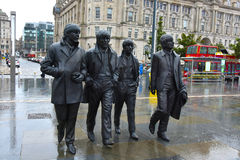 The Beatles. Bronze statue of the Beatles at the Waterfrontin Liverpool, UK. It was created by the sculporr Andrew Edwards. Th wether is typical english, it Stock Photography