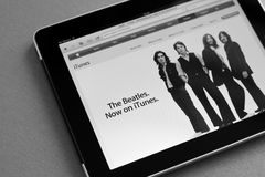 The Beatles now on iTunes. Apple Ipad shows iTunes home page with information that the Beatles music are now available for downloading. Processed in BW stock photo