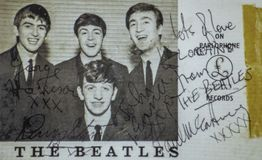 The Beatles postcard 1962. The Beatles were an English rock band formed in Liverpool in 1960. Photo taken in a Beatles book. This promotional photo card for the stock images