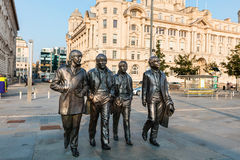 Beatles statue at the Liverpool Waterfront. LIVERPOOL, UK - AUGUST 18, 2016:  Bronze statue of the four Liverpool Beatles stands on Liverpool Waterfront by Royalty Free Stock Images