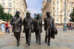 Beatles statue at the Liverpool Waterfront. LIVERPOOL, UK - AUGUST 18, 2016:  Bronze statue of the four Liverpool Beatles stands on Liverpool Waterfront by Royalty Free Stock Photos
