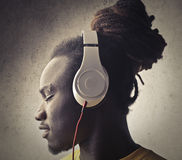 Beats. African boy listening to music with a big headphone Royalty Free Stock Photography