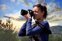 Beatutiful σκηνή ηλιοβασιλέματος φύσης φωτογραφίας νέων κοριτσιών με τη κάμερα και το φακό της Canon της Εκλεκτικά FO Στοκ Εικόνα