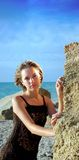 Beaty dichtbij rots op zonsondergangstrand Stock Foto