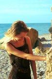 Beaty near rock on sunset beach smiling Royalty Free Stock Photo