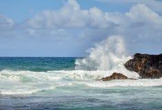 Beau éclabousse des vagues frappant le rivage pierreux Images stock