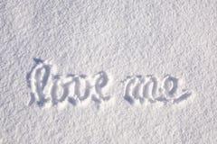 Beau aimez-moi écrit sur la neige Images stock