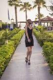 Beau amincissez la femme caucasienne convenable de brune dans de petits dres noirs Photos stock