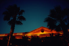 Beau bâtiment contre le ciel nocturne avec des silhouettes de palmiers Photo stock