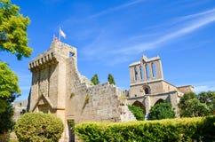 Beau bâtiment de l'abbaye médiévale de Bellapais prise avec le parc adjacent et avec le ciel bleu Les ruines du monast?re images stock