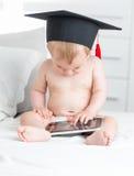 Beau bébé dans le chapeau d'obtention du diplôme utilisant le comprimé numérique Photographie stock
