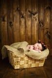 Beau bébé de sommeil nouveau-né dans le panier en osier sur un fond en bois Photos stock