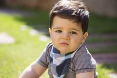 Beau bébé garçon brésilien dans l'herbe regardant la caméra Ser image stock
