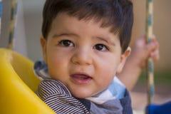 Beau bébé garçon brésilien regardant la caméra bébé sur le swin photos stock
