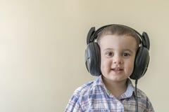 Beau bébé garçon dans de grands écouteurs Un garçon dans une chemise de plaid écoutant la musique Copiez l'espace Photos libres de droits