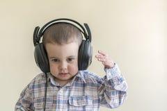 Beau bébé garçon dans de grands écouteurs Un garçon dans une chemise de plaid écoutant la musique Copiez l'espace Images libres de droits